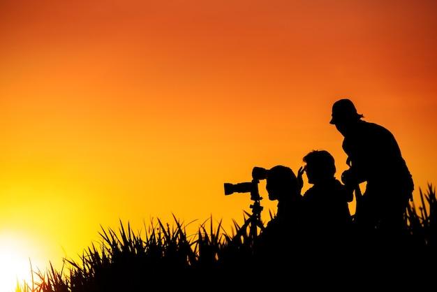 Silhouette del gruppo di fotografi su erba