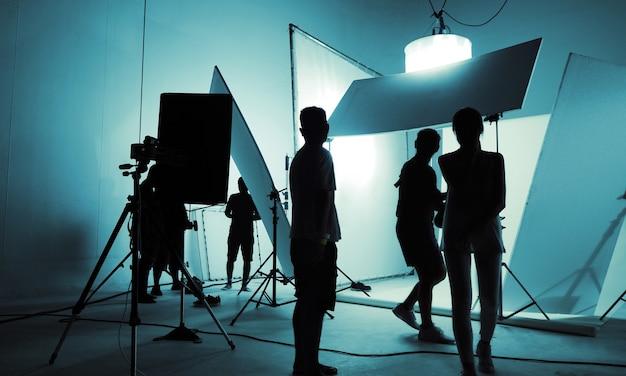 Il team della troupe di produzione della silhouette lavora in studio fotografico e flash di illuminazione e fari a led