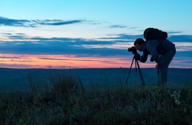 Silhouette di un fotografo professionista che utilizza un treppiede, scatta una foto di un paesaggio di montagna