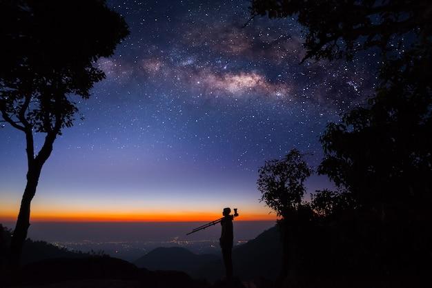 Silhouette di un fotografo professionista che fotografa una via lattea sulla montagna