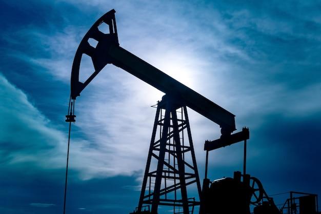 Silhouette di un pumpjack con pompa a pistone su un pozzo petrolifero sullo sfondo del cielo