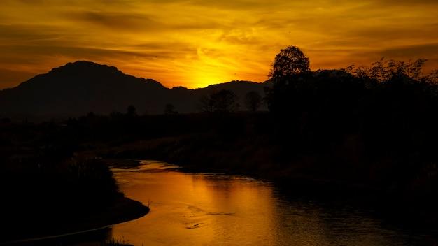 Silhouette e riflesso del sole e del fiume moei che confinano tra thailandia e birmania