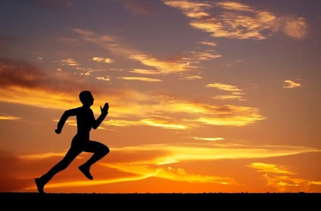 Siluetta dell'uomo che corre contro il cielo colorato. sagoma di uomo che corre su sfondo infuocato al tramonto