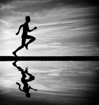 Siluetta dell'uomo corrente contro il cielo. siluetta dell'uomo che corre al tramonto. riflessione dell'acqua. bianco e nero. elemento di design.