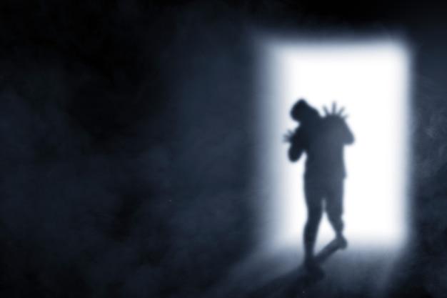 Sagoma di zombie spaventoso con sangue e ferita sul suo corpo proveniente dallo sfondo luminoso della porta