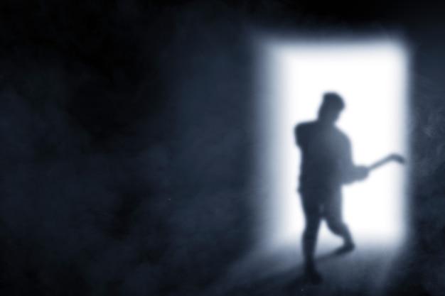 Sagoma di zombie spaventoso con sangue e ferita sul suo corpo che tiene la falce proveniente dallo sfondo luminoso della porta
