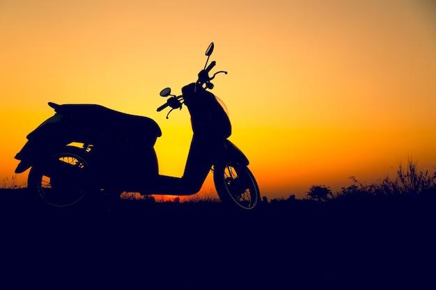 Profili il motorino che sta sul campo al tramonto