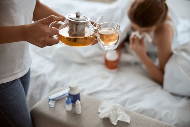 Silhouette di donna malata sdraiata sotto la coperta e che si soffia il naso