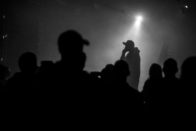 Una silhouette di cantante rap musicista durante il concerto dal vivo in condizioni di luce scura.