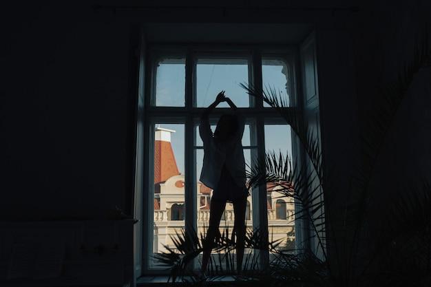 Siluetta della ragazza sottile con le mani in alto in piedi sul davanzale della finestra e balli a casa.