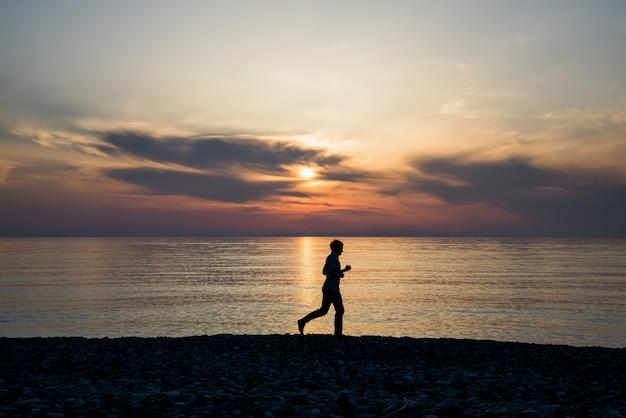 Siluetta dell'uomo attivo di sport che corre e che si esercita sulla spiaggia al tramonto