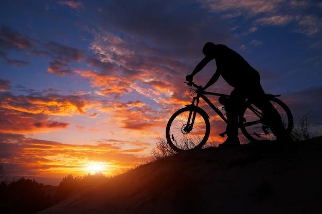 Siluetta della persona sportiva in bicicletta sul prato sul bellissimo tramonto. bicicletta di guida del giovane.