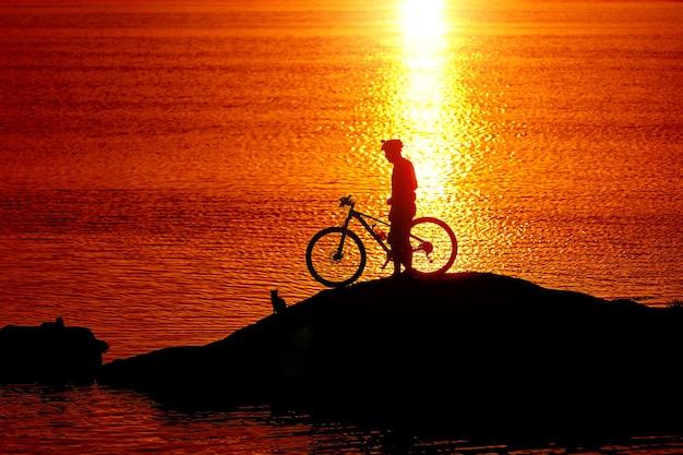 Siluetta di un ciclista sportivo in casco su una bici. concetto di stile di vita attivo.