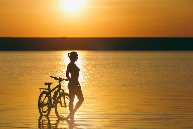La silhouette di una ragazza sportiva in un vestito in piedi vicino a una bicicletta in acqua al tramonto in una calda giornata estiva. concetto di forma fisica.