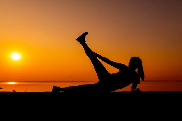Donna sportiva della siluetta con il tramonto. attività sana e di esercizio. stile di vita e ricreazione.