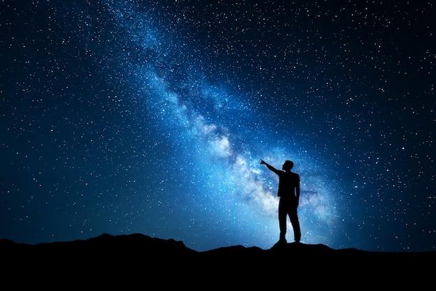 Silhouette di un giovane in piedi che punta il dito nel cielo stellato notturno sullo sfondo blu della via lattea.