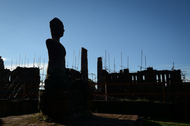Silhouette di una statua del buddha, in fase di restauro in un antico tempio di phra nakhon si ayutthaya