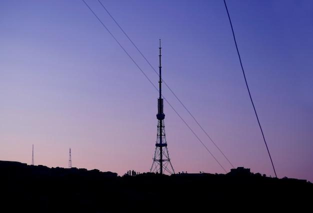 Silhouette della torre delle telecomunicazioni con linee elettriche contro il cielo mattutino