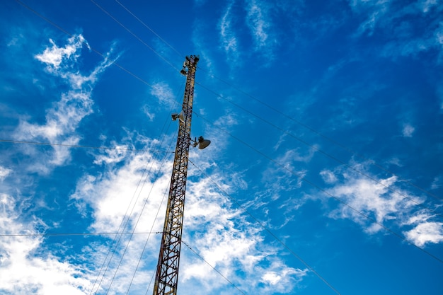 La sagoma di una torre di telecomunicazioni sullo sfondo di un cielo azzurro straordinariamente bello con nuvole bianche luminose sfocate