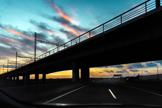 Silhouette di un ponte ferroviario su un'autostrada, visto dall'abitacolo di un'auto che attraversa la città al tramonto.
