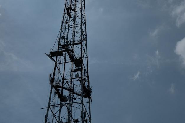 Profili le torri di trasmissione e comunicazione del segnale tv sullo sfondo di un cielo nuvoloso