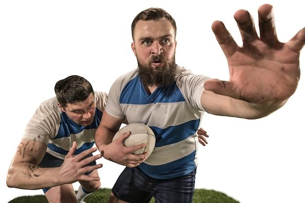 La siluetta di due giocatori caucasici dell'uomo di rugby isolati su fondo bianco. colpo dello studio dell'uomo in forma in movimento o movimento con la palla. concetto di gioco e azione. incredibile sforzo di tutte le forze