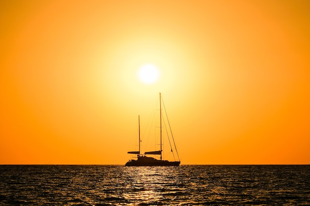 Silhouette di uno yacht a due alberi in mare sullo sfondo dell'orizzonte del sole al tramonto.