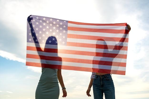 Silhouette di due giovani amici donne che tengono la bandiera nazionale usa nelle loro mani in piedi insieme. ragazze patriottiche che celebrano il giorno dell'indipendenza degli stati uniti.