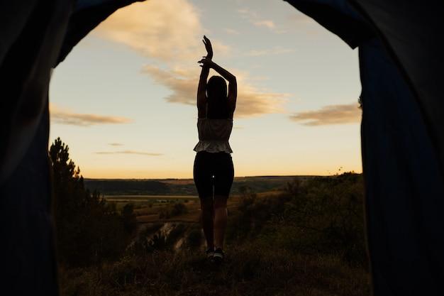 Silhouette e vista dal retro di una donna, in piedi su una montagna con le mani in alto e ammira la splendida vista.