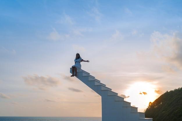 Profili i capelli ventosi la donna asiatica si siede sopra la scala di legno con il cielo di tramonto nei precedenti, libertà, concetto di successo