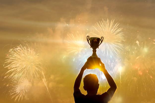 Sagoma di un uomo vincente che tiene il premio coppa trofeo campione d'oro.