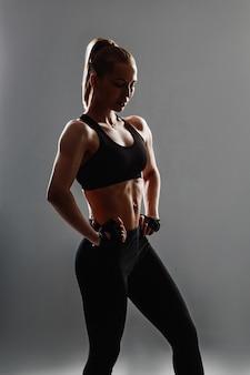 Una silhouette di una donna in abiti sportivi neri in posa, che mostra i suoi muscoli.