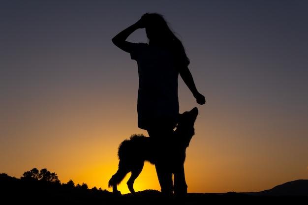 Silhouette di donna che gioca con un cane al tramonto di fronte a un lago amore per gli animali copia spazio
