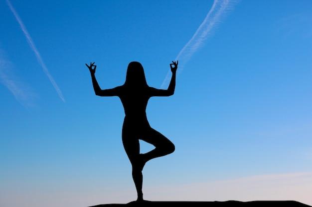 Silhouette di donna a praticare yoga durante il tramonto in riva al mare.
