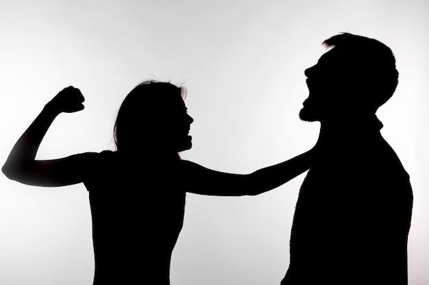 Silhouette di una donna che schiaffeggia un uomo.