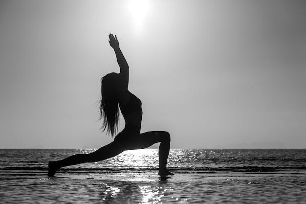 Siluetta della donna che sta alla posa di yoga sulla spiaggia tropicale durante il tramonto. ragazza caucasica che pratica yoga vicino all'acqua di mare. bianco e nero