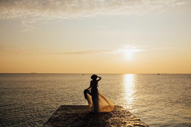 La siluetta di una donna guarda il tramonto su un mare o un oceano