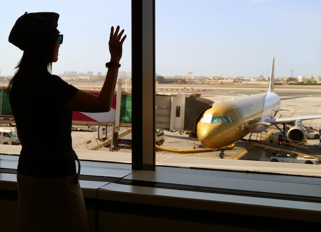 Siluetta di una mano d'ondeggiamento della donna all'aeroplano all'aeroporto