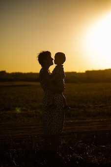 Silhouette di una donna con un bambino in braccio su uno sfondo tramonto. la mamma tiene il bambino tra le braccia sullo sfondo del tramonto. silhouette