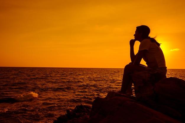Donne della siluetta che si siedono da sole sulla roccia. salute mentale, disturbo da stress post-traumatico e prevenzione del suicidio.