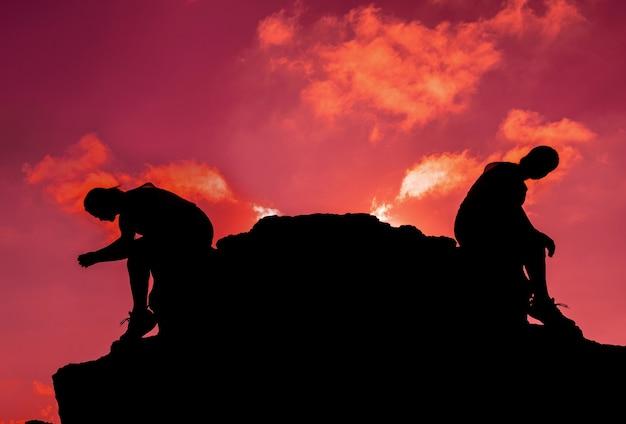 Donne della siluetta che si siedono sulla roccia. salute mentale, disturbo da stress post-traumatico e prevenzione del suicidio.