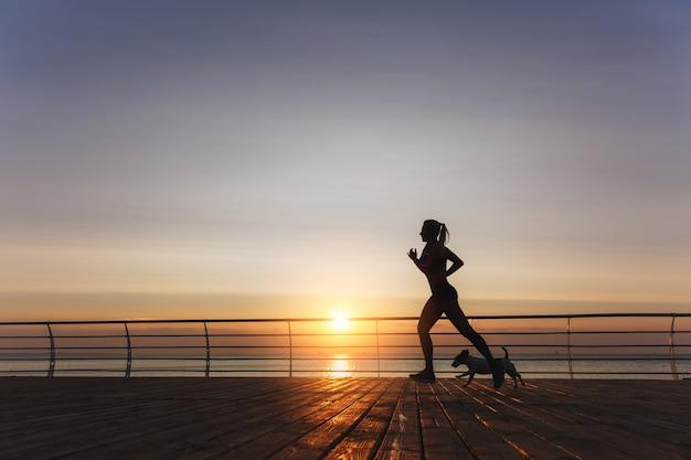La silhouette di una giovane bella ragazza atletica con lunghi capelli biondi in cuffia che corre all'alba sul mare con il suo cane