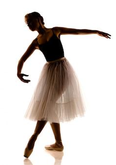 La siluetta di giovane bella ballerina in tutu bianco e scarpe da punta che fanno la posa di dancing