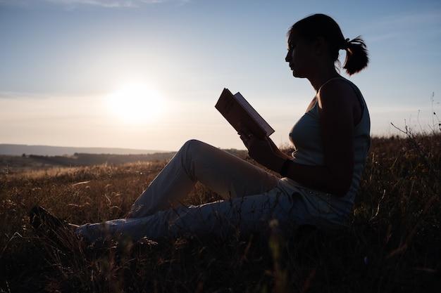 Siluetta di una giovane bella donna all'alba seduto per terra e fissando attentamente il libro aperto