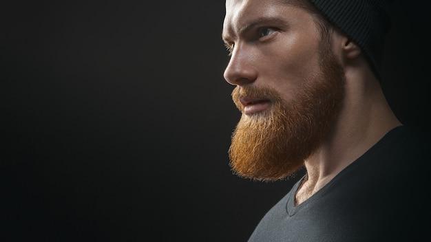 Siluetta di giovane hipster uomo barbuto bello fiducioso che indossa il cappello lavorato a maglia nero. bel giovane uomo barbuto in maglietta nera