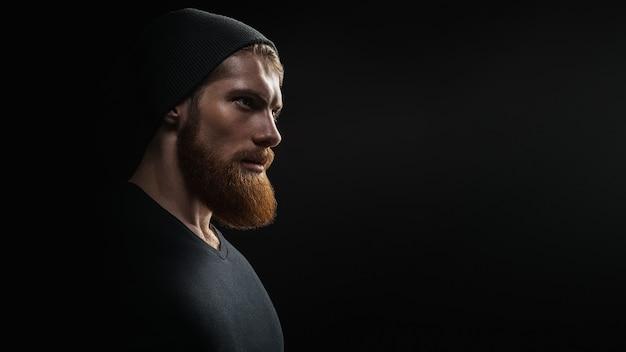 Siluetta di giovane hipster uomo barbuto bello fiducioso che indossa il cappello lavorato a maglia nero. studio girato su sfondo scuro immagine con spazio di copia gratuita