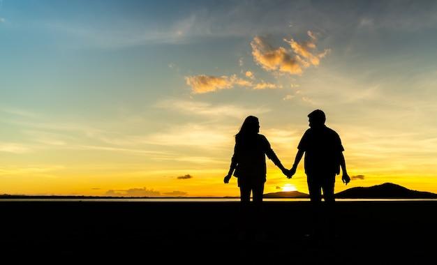 Siluetta di giovane coppia che si tiene per mano nel campo al tramonto