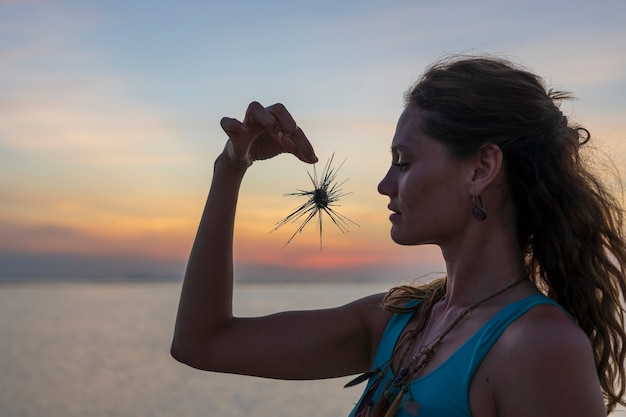 Silhouette di una giovane ragazza che tiene in mano il riccio di mare durante il tramonto sulla spiaggia vicino all'acqua di mare, primo piano