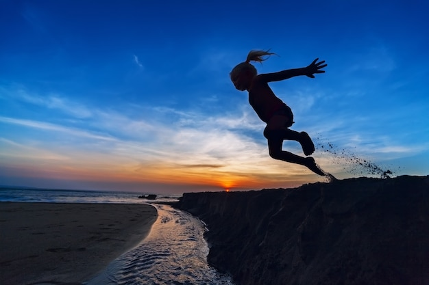 Siluetta della ragazza che salta in aria da una scogliera di sabbia sulla spiaggia al tramonto, cielo colorato