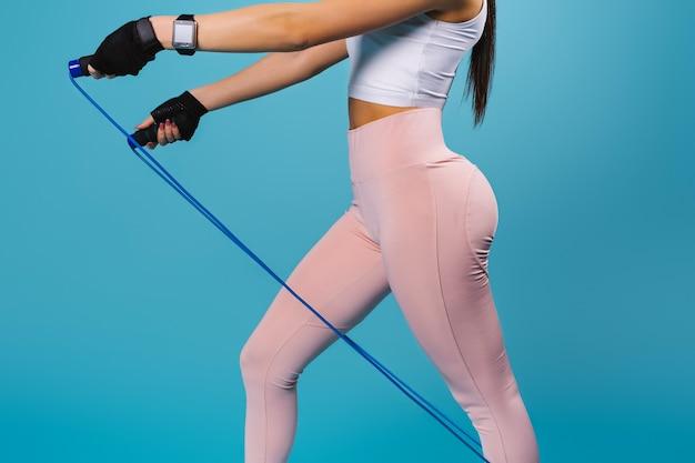 Siluetta di una giovane ragazza con le natiche pompate in leggings con una corda per saltare su un blu